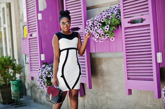 Afrikaans amerikaans meisje in glazen, zwart-witte kleding en handtas die tegen purpere vensters wordt gesteld.