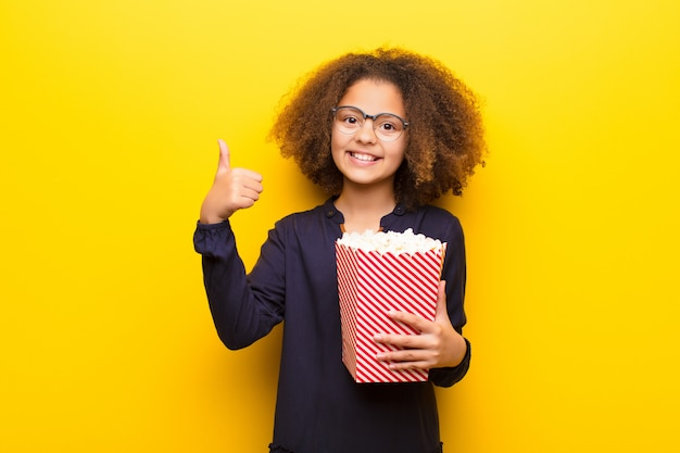 Afrikaans amerikaans meisje tegen vlakke muur die een emmer popcorns houdt