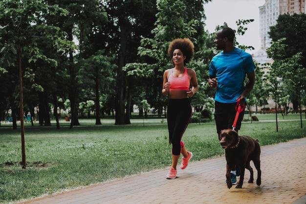 Afrikaans amerikaans paar in sportkleding lopen hond