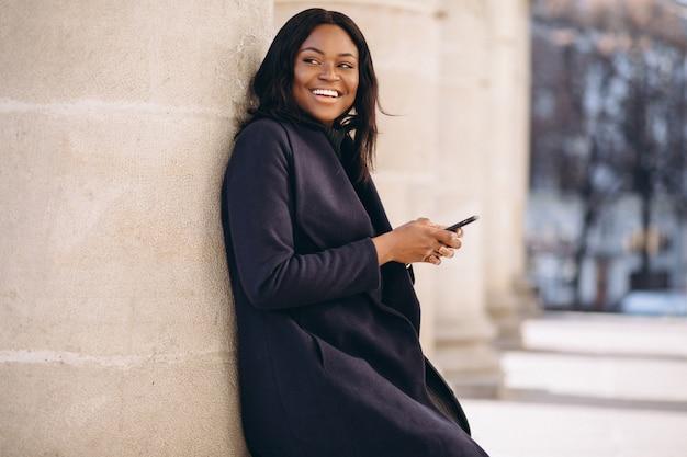 Afrikaans amerikaans studentenmeisje met telefoon door de universiteit