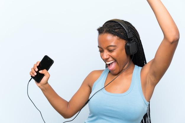 Afrikaans amerikaans tienermeisje met lang gevlecht haar het luisteren muziek met mobiel en dansen