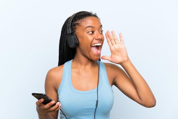 Afrikaans amerikaans tienermeisje met lang gevlecht haar het luisteren muziek met mobiel schreeuwend met wijd open mond
