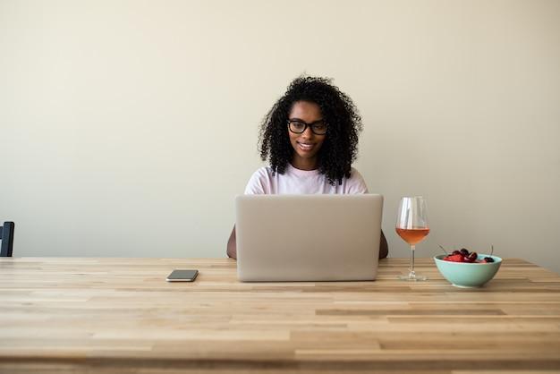 Afrikaans amerikaans wijfje die freelancer laptop thuis met behulp van