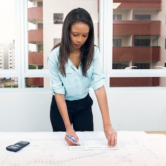 Afrikaans-amerikaanse dame met pen en liniaal dichtbij plan op tafel
