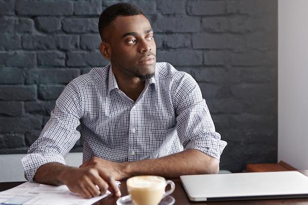 Afrikaans-amerikaanse ondernemer draagt shirt met opgerolde mouwen kijkt door raam