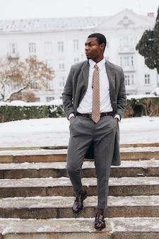 Afrikaans - amerikaanse zakenman die smartphone in de sneeuwstraat van de de winterstad gebruiken