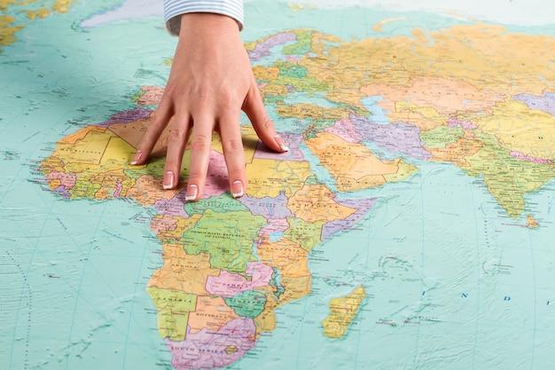 Afrikaans continent op wereldkaart. vrouwelijke hand toont afrikaans continent. briefing bij inlichtingendienst. zoeken en werven.