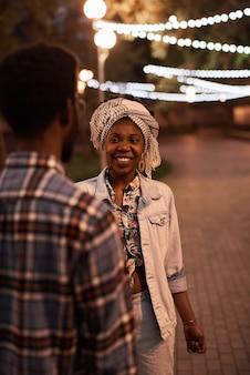 Afrikaans jong stel dat 's avonds samen in het park loopt