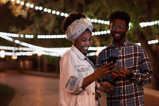 Afrikaans jong stel dat samen mobiele telefoon gebruikt terwijl ze 's avonds in het park staan