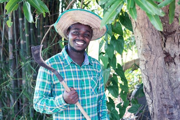 Afrikaans landbouwersmens die mes houden om het groene blad van boom te snijden