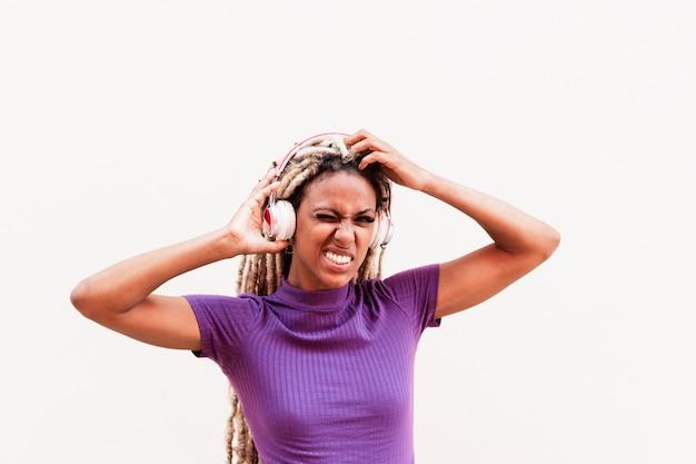 Afrikaans meisje bewegende blonde dreadlocks haar dragen tijdens het luisteren muziek afspeellijst met koptelefoon
