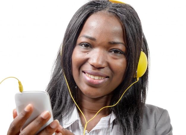 Afrikaans meisje dat mobiele telefoon houdt en aan muziek luistert