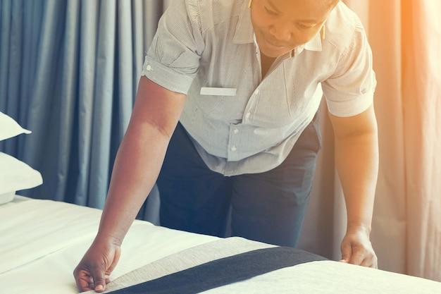 Afrikaans meisje die bed in hotelruimte maken. personeel is gek op bed. afrikaanse huishoudster die bed maakt.