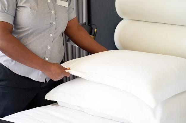 Afrikaans meisje die bed in hotelruimte maken. personeel meid opmaken bed. afrikaanse huishoudster die bed maakt.