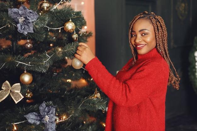 Afrikaans meisje in een kerstversiering / vrouw in een rode trui. nieuwjaar concept.