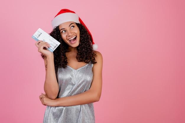 Afrikaans meisje met vliegtuigkaartjes die kerstmishoed dragen die over roze wordt geïsoleerd