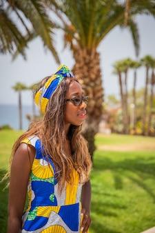 Afrikaans meisje poseert gekleed in haar afrikaanse jurk op een exotische locatie
