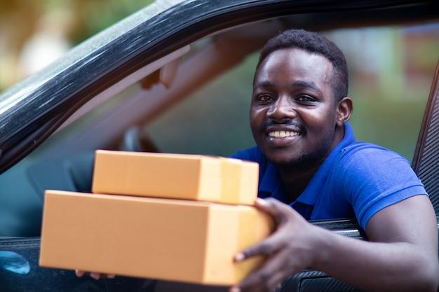 Afrikaans mensen dragend pakket van leveringsauto