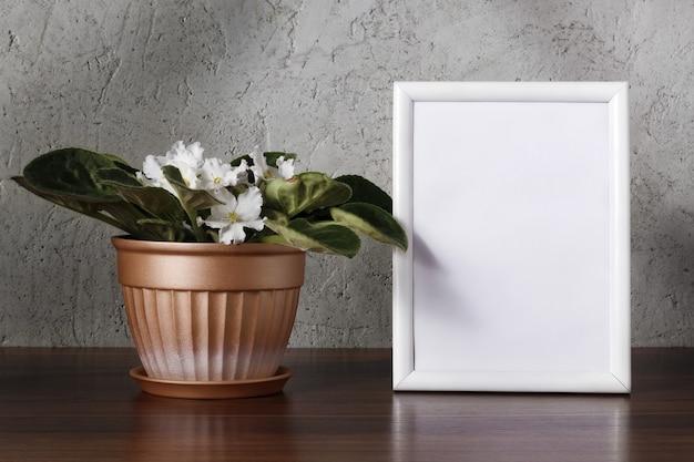 Afrikaans viooltje met witte bloemen in bloempot en wit houten frame op houten plank in de buurt van muur. interieur achtergrond.