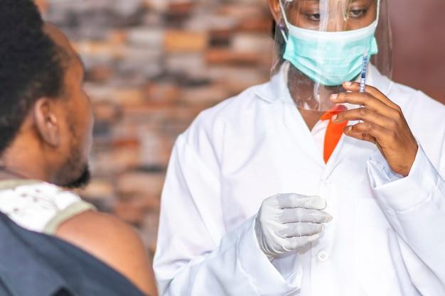 Afrikaans vrouwelijk medisch personeel dat een vaccinspuit vasthoudt en zich klaarmaakt om het toe te dienen aan een jonge zwarte man