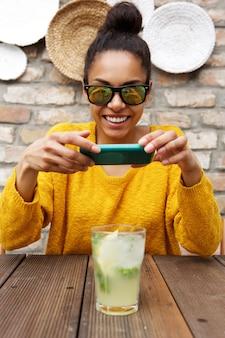 Afrikaans wijfje dat beeld van een drank neemt bij koffie