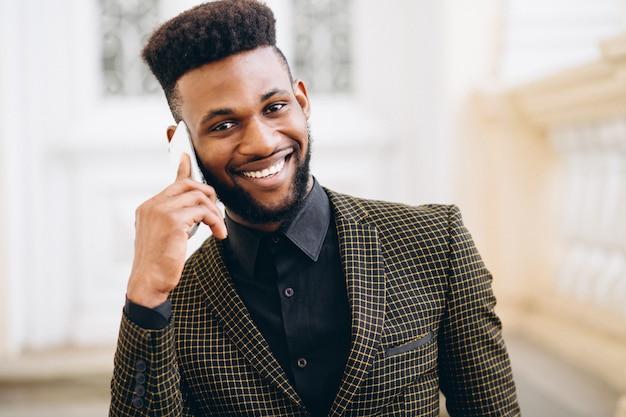 Afrikaanse amerikaanse bedrijfsmens die op de telefoon spreekt