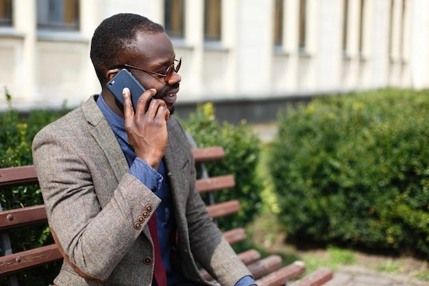 Afrikaanse amerikaanse bedrijfsmensbesprekingen op de smartphonezitting op de bank buiten
