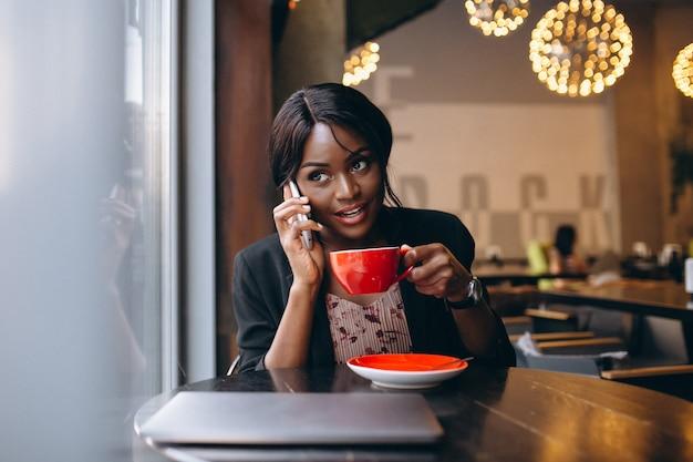 Afrikaanse amerikaanse bedrijfsvrouw die in een koffie werkt