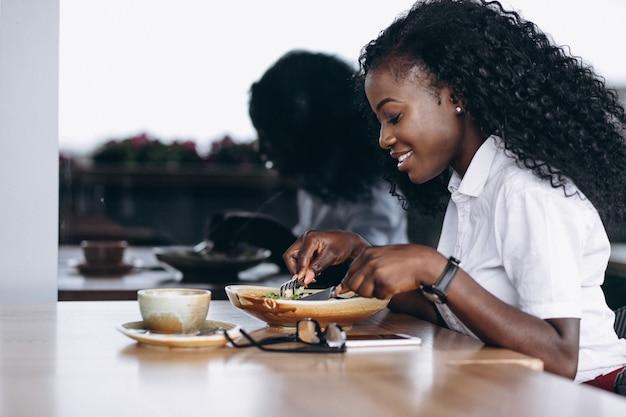 Afrikaanse amerikaanse bedrijfsvrouw die salade in een koffie eet