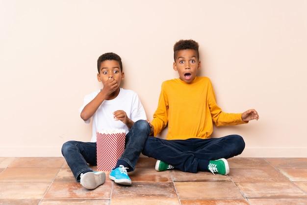 Afrikaanse amerikaanse broers die popcorns houden en verrassingsgebaar doen