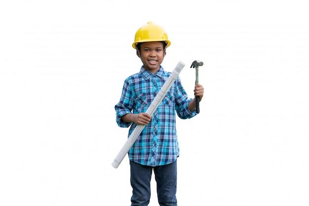 Afrikaanse amerikaanse de holdingsblauwdrukken en hamer die van de jongensingenieur een gele veiligheidshelm op witte geïsoleerde achtergrond dragen