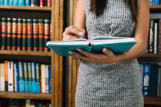 Afrikaanse amerikaanse jonge dame met boek en pen