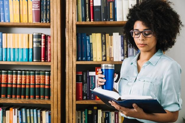 Afrikaanse amerikaanse jonge dame met thermosflessen en boek