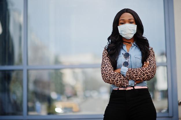 Afrikaanse amerikaanse jonge vrijwilligersvrouw die gezichtsmasker in openlucht draagt. coronavirus-quarantaine en wereldwijde pandemie.