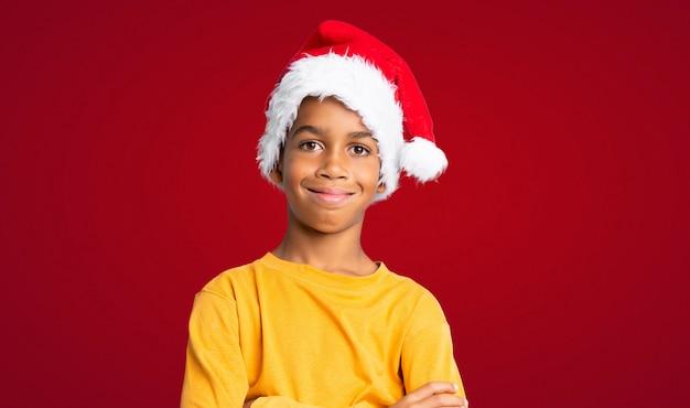 Afrikaanse amerikaanse jongen die met kerstmishoed veel over rode muur glimlacht