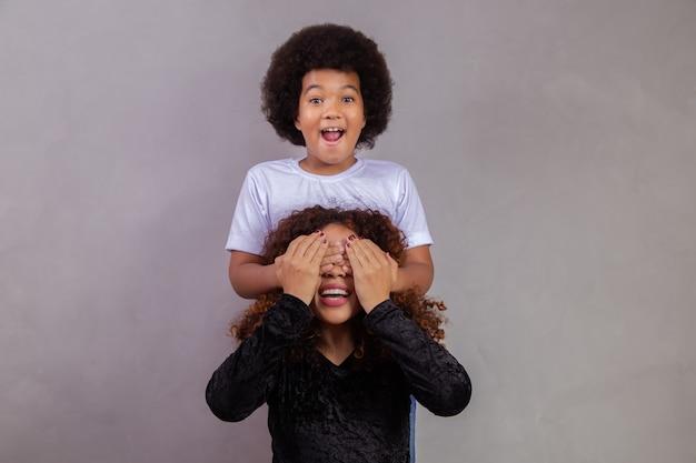 Afrikaanse amerikaanse jongen die zijn moeder gesloten ogen houdt. grijze achtergrond. moederdag. braziliaanse familie.