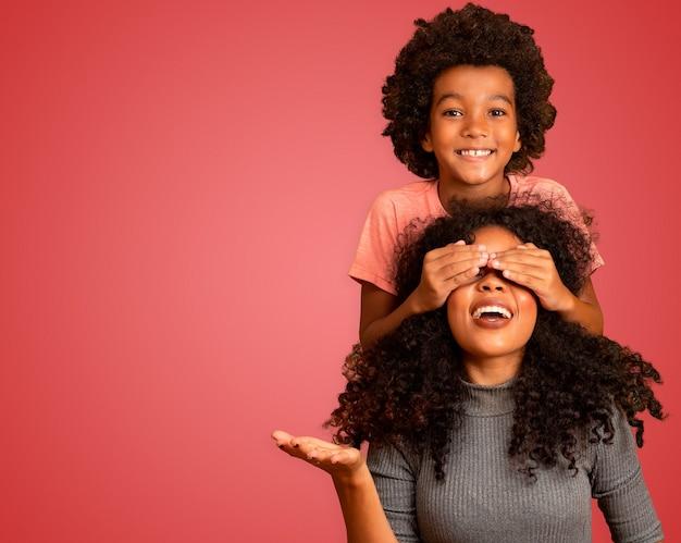 Afrikaanse amerikaanse jongen die zijn moeder gesloten ogen houdt. rode achtergrond. moederdag. braziliaanse familie.
