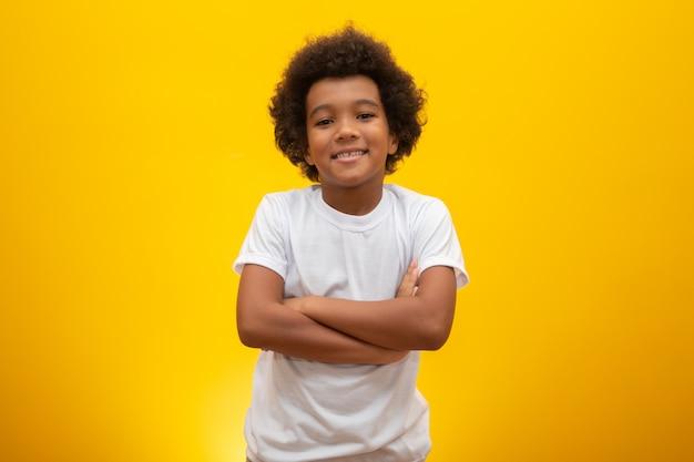 Afrikaanse amerikaanse jongen met zwart machtshaar op geel. glimlachend zwart jong geitje met een zwart machtshaar. zwarte jongen met zwart haar. afrikaanse afkomst.