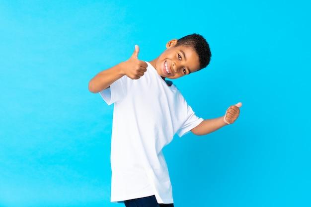 Afrikaanse amerikaanse jongen over geïsoleerd blauw met omhoog duimen omdat er iets goeds is gebeurd