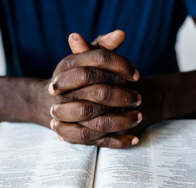 Afrikaanse amerikaanse mannelijke handen die op een open bijbel rusten