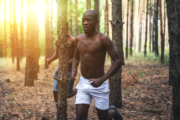 Afrikaanse amerikaanse mannen die in het hout bij zonsondergang lopen. atleten joggen