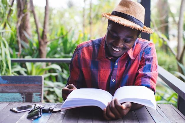 Afrikaanse amerikaanse mens die een boek met koffie, sleutel, smartphone en groene natuurlijke achtergrond leest.