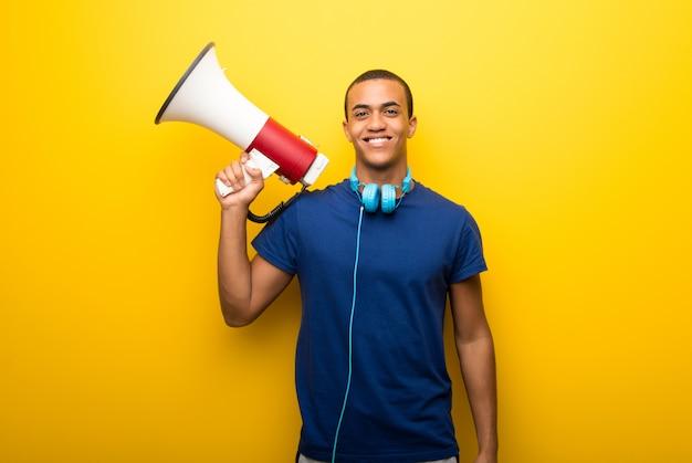 Afrikaanse amerikaanse mens die met blauwe t-shirt op gele achtergrond een megafoon houdt