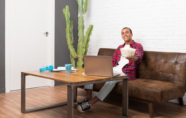 Afrikaanse amerikaanse mens die met laptop in de woonkamer popcorns eet