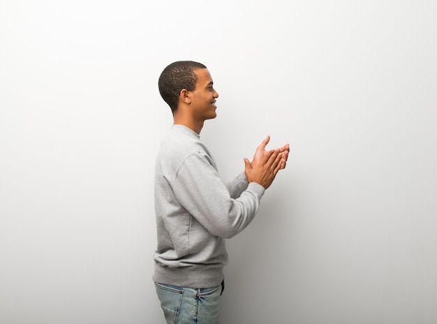 Afrikaanse amerikaanse mens die op witte muurachtergrond na presentatie in een conferentie toejuichen