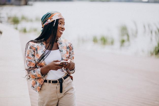 Afrikaanse amerikaanse mens die telefoon in het park met behulp van