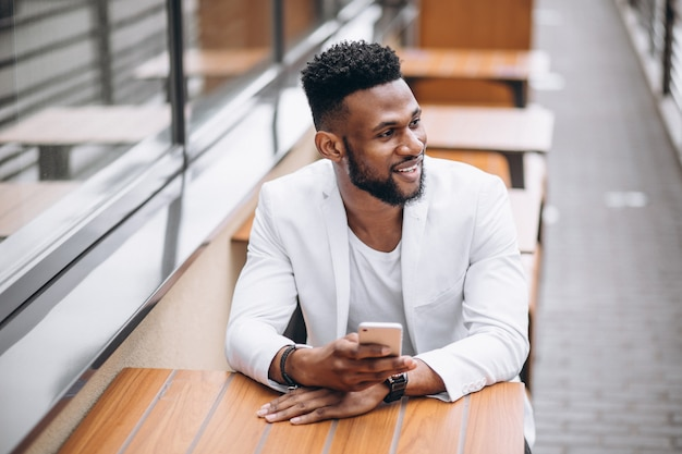 Afrikaanse amerikaanse mens die telefoon met behulp van