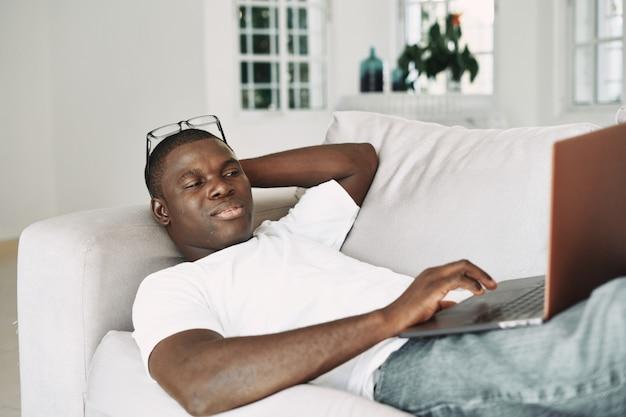 Afrikaanse amerikaanse mens die thuis freelancer laptop werkt