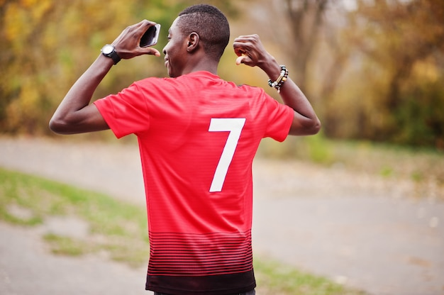 Afrikaanse amerikaanse mens in de rode t-shirt van de voetbalsport met 7 aantal tegen de herfstpark.