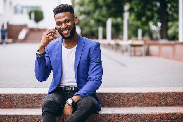 Afrikaanse amerikaanse mens in matroos die telefoon met behulp van